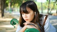 Música que escucha emocionalmente triste de la mujer asiática triste del inconformista joven en auriculares con smartphone