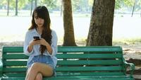 Nette Frau liest angenehme Textnachricht am Handy beim Sitzen im Park am warmen Frühlingstag