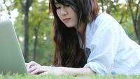 Ung asiatisk kvinna ben på grönt gräs med öppen bärbar dator.