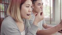 Aantrekkelijk jong Aziatisch paar dat bij lijst met krant en celtelefoon wordt afgeleid terwijl het eten van ontbijt.