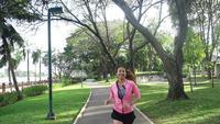 Zeitlupe - junge asiatische Frau, die auf Bürgersteig am Morgen läuft.