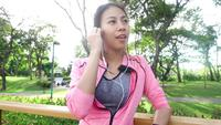 Slow motion - Asian beautiful woman in fitness outfits are using a smartwatch for listen to music, talking on the phone after running in the park.