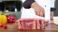 Ciérrese para arriba del cocinero o del cocinero gastrónomo que sazona el pedazo fresco de la pieza de la tienda de delicatessen de carne de vaca con la sal de mar y las pimientas picantes puestas a tierra.