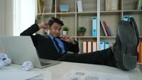 Müder und fauler junger Mann, der im Büro sitzt