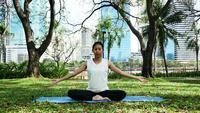 Young asian woman yoga outdoors keep calm and meditates while practicing yoga to explore the inner peace.