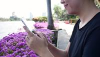 Beautiful asian young woman sitting at bench in park using smartphone for talking, reading and texting.