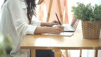 Vacker ung leende asiatisk kvinna som arbetar på laptop medan hemma på kontorsarbete utrymme.