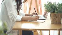 Lächelnde Asiatin der schönen Junge, die an Laptop während zu Hause im Büroarbeitsplatz arbeitet.