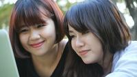 Mulheres asiáticas novas que encontram-se na grama e que usam o portátil e datilografando.