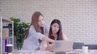 Zwei junge asiatische Frauen, die zusammen in einem Büro an ihrem Kleinbetrieb sitzen, einen Bericht oder eine Schreibarbeit mit erfreutem Lächeln lesend.