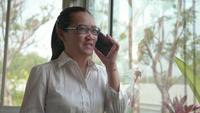 Aziatische vrouwenhanden die mobiele slimme telefoon met behulp van bij bureauvenster.