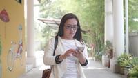 Gafas asiáticas de la mujer i que hablan en el teléfono celular mientras que camina.
