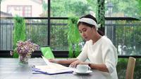 Vacker ung leende asiatisk kvinna som arbetar på laptop medan du sitter i vardagsrummet hemma.