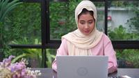 Vacker ung leende asiatisk muslimsk kvinna som arbetar på laptop sitter i vardagsrummet hemma.