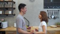 Beautiful happy asian couple are dancing in the kitchen at home.