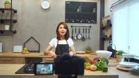 Young asian woman in kitchen recording video on camera.