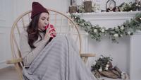 Vacker attraktiv asiatisk kvinna som håller en varm kopp kaffe eller te medan hon ligger på stolen när hon slappar av i sitt vardagsrum hemma.
