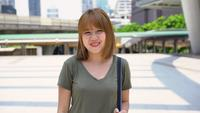 Attractive young smiling Asian woman outdoors portrait in the city real people series.