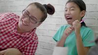 Mãe asiática que joga com as crianças no assoalho da sala de visitas.