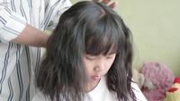Família asiática com a mãe que escova seu cabelo pequeno da filha.