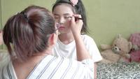Familia asiática con la madre que hace maquillaje a su niña en el cuarto.