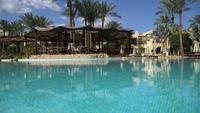 Sunny Hotel Resort mit blauem Luxuspool, Wasserrutschen, Palmen, Sonnenschirmen und Sonnenliegen in Ägypten. Reichhaltiger Urlaub im sonnigen Resort. Leeres ägyptisches Hotel mit Pool