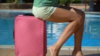 Young woman with pink case near swimming pool in hotel. Travel vacation concept