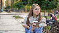 Close-up of the face of woman who drinks hot tea or coffee in autumn park, she wears knitted scarf. girl drinks coffee for good mood from mug