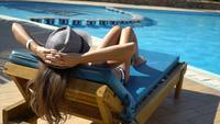 Pretty woman relaxing in a lounger near of the swimming pool
