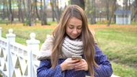 Caucasian woman with knitten scarf using smart phone, typing something during walking in autumn park