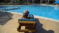 Mulher magro despreocupada descontrai e sunbathes perto da piscina em um dia de verão