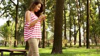 Beautiful girl is walking in city park and using smartphone, young woman is holding device and touching screen, summer nature is visible