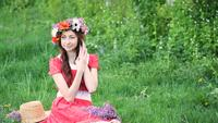 Beautiful woman with wreath picks flowers on meadow. Happy woman in spring or summer season. I love to work with plants