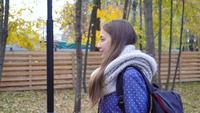 A jovem mulher bonita veste o lenço feito malha e o passeio no parque do outono. Movimento de vídeo 4k