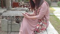 Mujer asiática que usa medios sociales en parque.