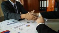 Business partners handshaking after signing contract at office.