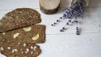 Bread with flaxseeds and almonds on a white wooden background.