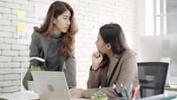 Two young Asian businesswomen working together in office at small business sitting reading a report.