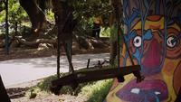 Balançoire en bois dans un parc public avec des graffitis en arrière-plan