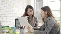 Two young Asian businesswomen working together in office.
