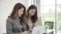 Two Asian young creative businesswomen holding a cup of coffee and working on laptop