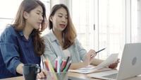 Asiatische Geschäftsfrauen in der intelligenten Freizeitkleidung, die an Laptop beim Sitzen auf Schreibtisch im Büro arbeitet.