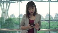 Attractive casual happy young Asian woman in international airport.