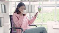 Mujer asiática en ropa de sport elegante usando smartphone y bebiendo la taza de café caliente en oficina.