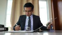 Homme d'affaires signant un contrat commercial sur des documents papier.