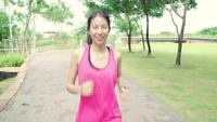 Mujer asiática del corredor en la ropa de los deportes que corre y que activa en la calle en parque urbano de la ciudad.
