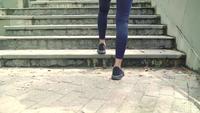 Asiatische Läuferfrau in der Sportkleidung, die auf Straße im städtischen Stadtpark läuft und rüttelt.