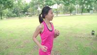 Zeitlupe - gesunde schöne junge asiatische Läuferfrau im Park.
