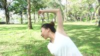 Zeitlupe - junges asiatisches Frauenyoga behalten draußen Ruhe und meditiert beim Üben von Yoga, um inneren Frieden zu erforschen.