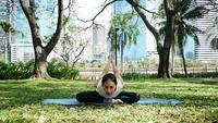 Junges asiatisches Frauenyoga draußen behalten Ruhe und meditiert beim Üben von Yoga.